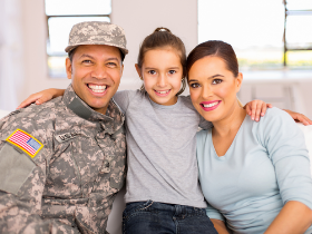 Family sitting on couch. Male adult in uniform