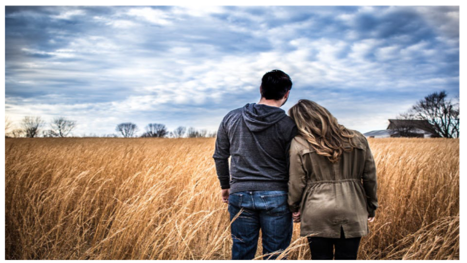 two people standing in field
