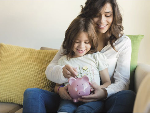 Mom with child putting money into a piggy bank